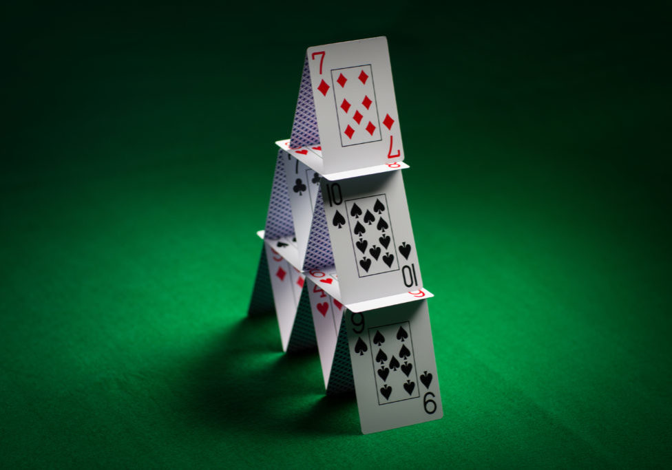 house of playing cards on green table cloth